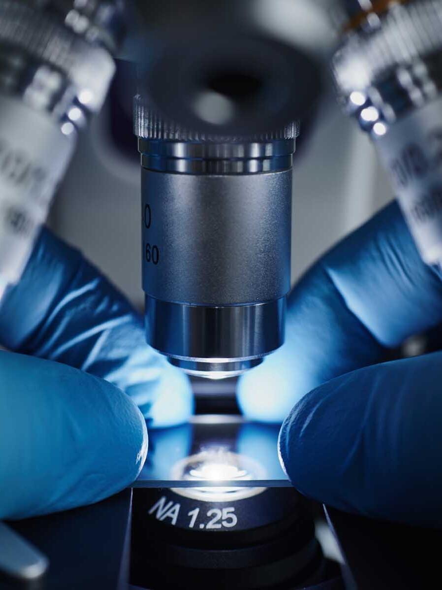 Mains d'un scientifique avec un microscope